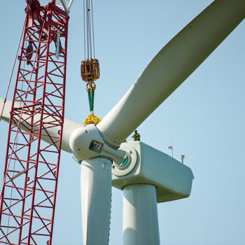 Wind turbine being installed with a red crane against a clear blue sky