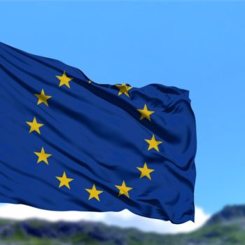 EU flag in front of green mountains