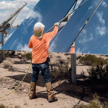 A worker cleans solar panels in the desert