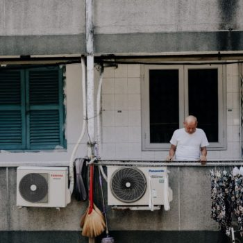 Man stands on a balcony of flat block with air conditioning units. Photo by Michu Đăng Quang on Unsplash