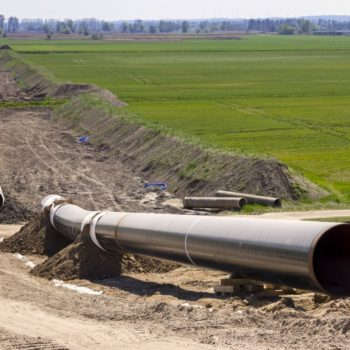 Unassembled gas pipeline lies on a field in Germany, ready to be installed