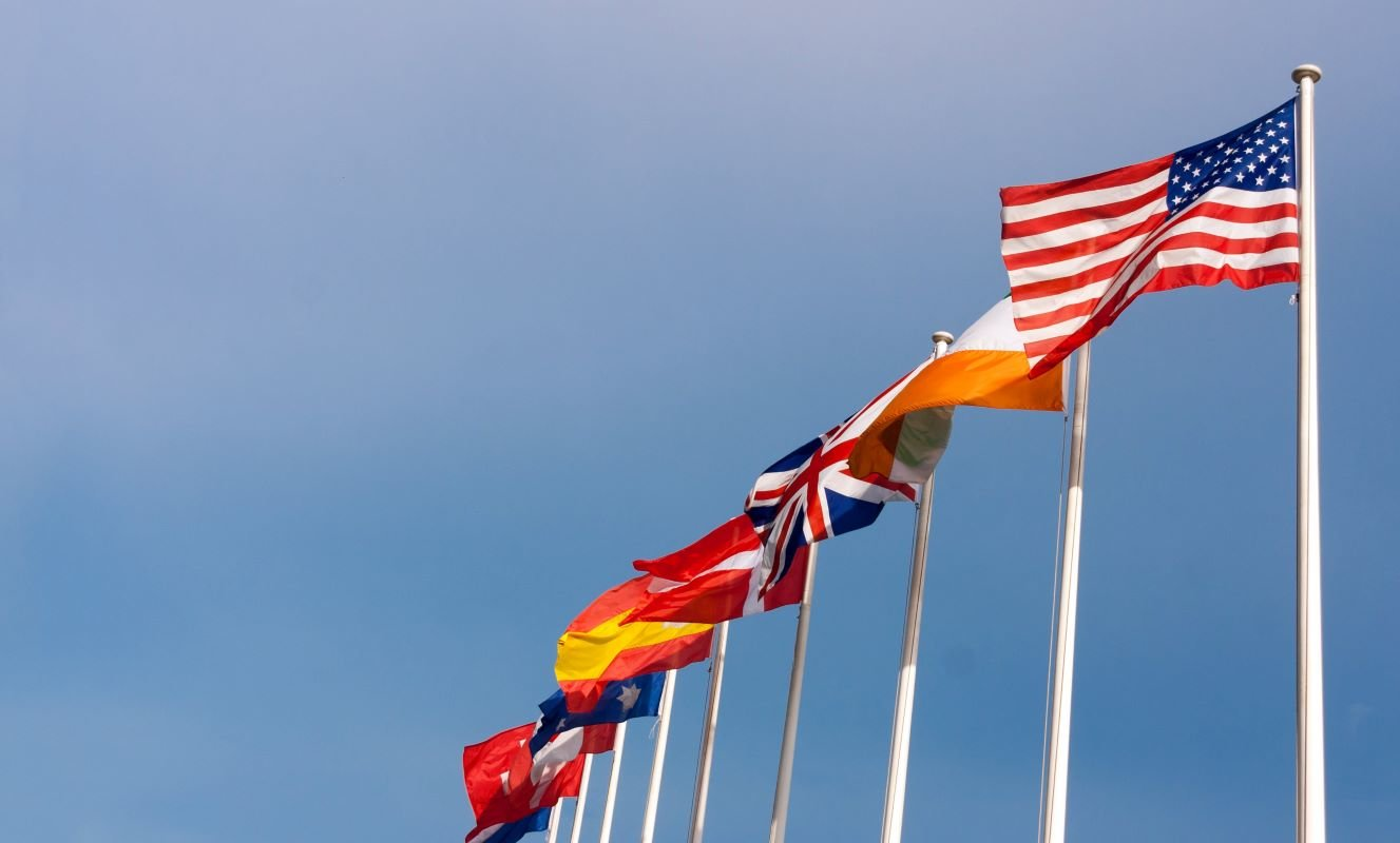 International US and global flags on blue sky